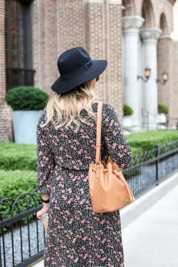 Bows & Sequins wearing a black hat, an Old Navy floral dress, and a Brahmin leather bag.