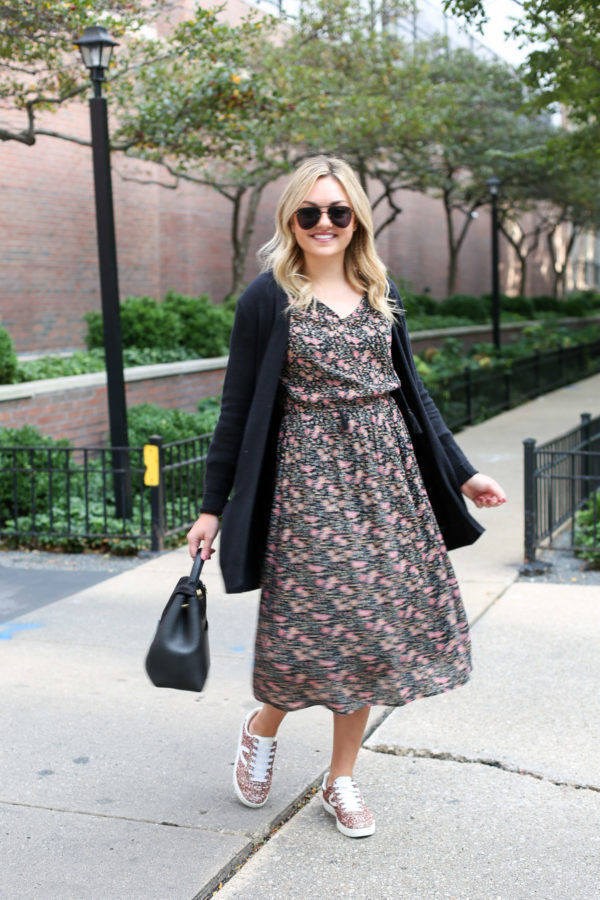 Bows & Sequiins wearing a black Old Navy cardigan, a midi floral dress, and Tretorn pink glitter sneakers with a top-handle black leather handbag.