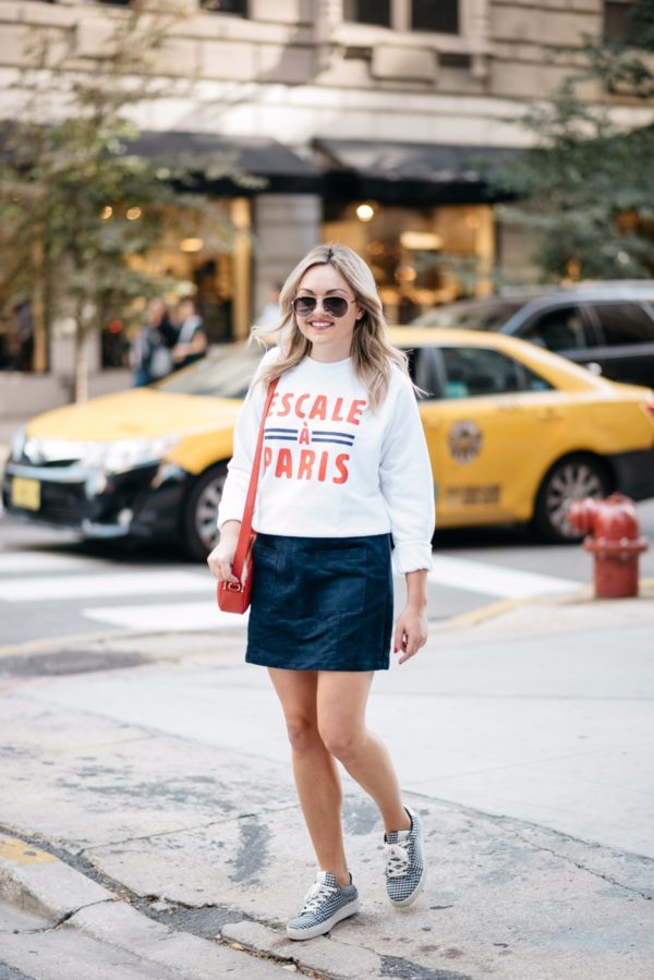 Chicago lifestyle blogger Bows & Sequins wearing Gucci aviators, a French Disorder Paris sweatshirt, and an Old Navy blue suede skirt and Claudie Pierlot gingham sneakers with a Talbots red leather bag.