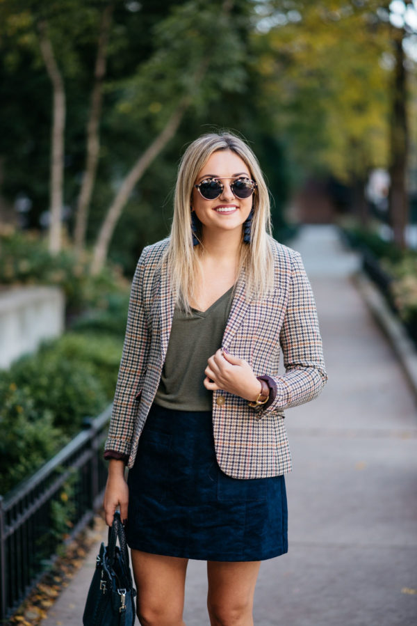 Chicago lifestyle blogger Bows & Sequins styling work wear: Illesteva sunglasses, Baublebar navy tassel earrings, Joules houndstooth blazer, Express olive green v-neck tee, and Old Navy blue suede skirt with a Kate Spade bag and a Gucci cuff bracelet via Switch.