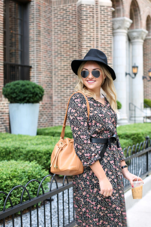 Jessica from the fashion-focused lifestyle blog Bows & Sequins wearing an Old Navy black hat, aviators, a floral dress, black Madewell belt, and a Brahmin leather bag.