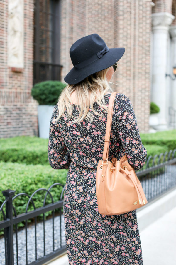 Bows & Sequins wearing a black Old Navy hat, a floral dress, and a Brahmin leather bucket bag.