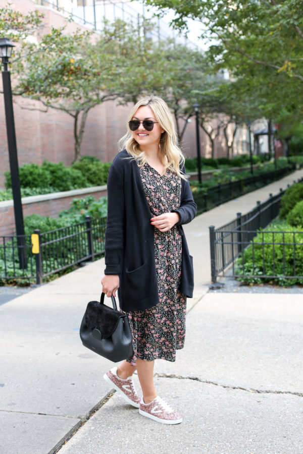Bows & Sequins wearing a long black cardigan, a floral midi dress, glitter sneakers, and a Polene top-handle leather bag.
