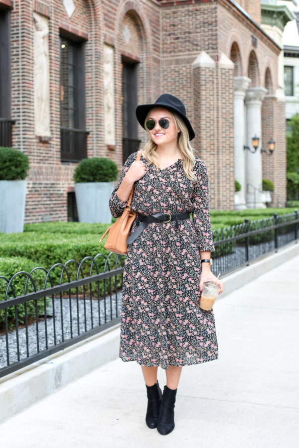 Chicago style blogger Bows & Sequins wearing a black Old Navy hat, a floral midi dress, a black Madewell leather belt, and ankle booties.