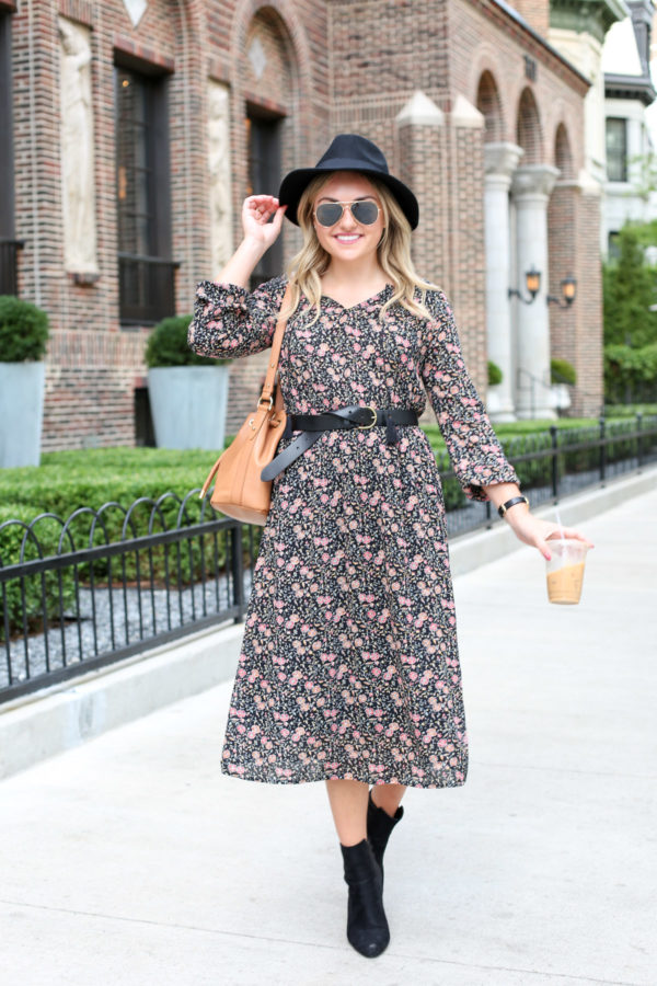 Bows & Sequins wearing a black hat, a floral midi dress, a black leather Madewell belt, black booties, and a Brahmin leather bag.