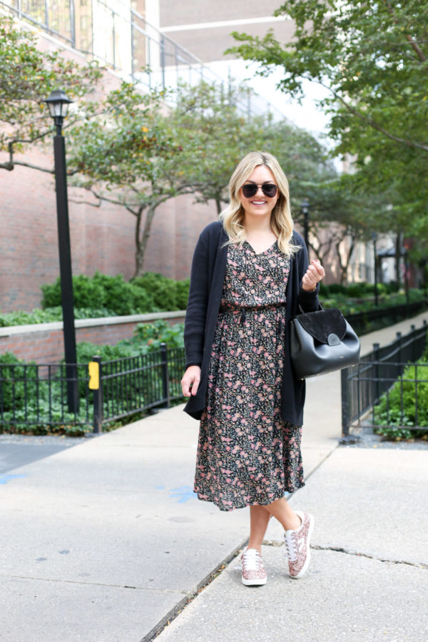 Fashion and lifestyle blogger Bows & Sequins wearing a floral midi dress with a black cardigan, a black belt, and pink glitter sneakers.