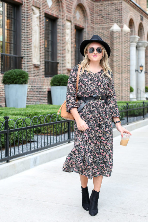 Chicago blogger Bows & Sequins wearing a black hat, Ray-Ban aviators, a floral midi dress, a black leather belt, and ankle booties.