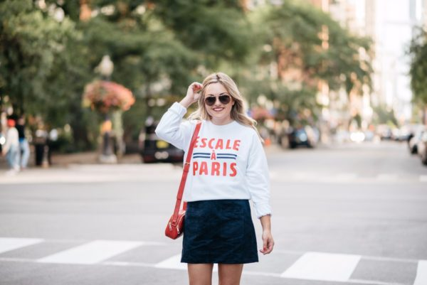 Bows & Sequins wearing a French Disorder Parisian-inspired sweatshirt with a red leather bag from Talbots and a navy suede skirt.