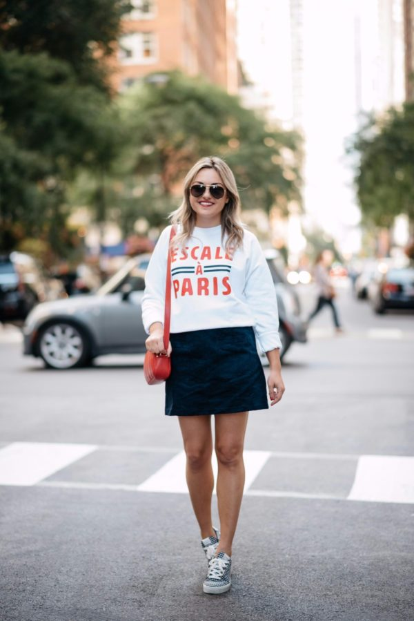 Fashion and travel writer Bows & Sequins wearing a French Disorder sweatshirt with an Old Navy blue suede skirt, a Talbots red leather bag, aviators, and Claudie Pierlot gingham sneakers.