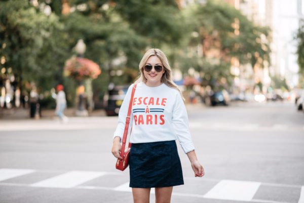 Chicago blogger Bows & Sequins wearing a French Disorder sweatshirt, an Old Navy blue suede skirt, Gucci aviators, and a Talbots red leather bag.