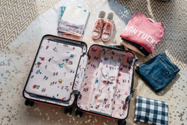 Travel writer Bows & Sequins sharing packing tips for a carry on suitcase.