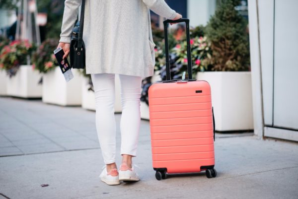 Bows & Sequins wearing a white outfit for the airport with a pink Away x Gray Malin suitcase.