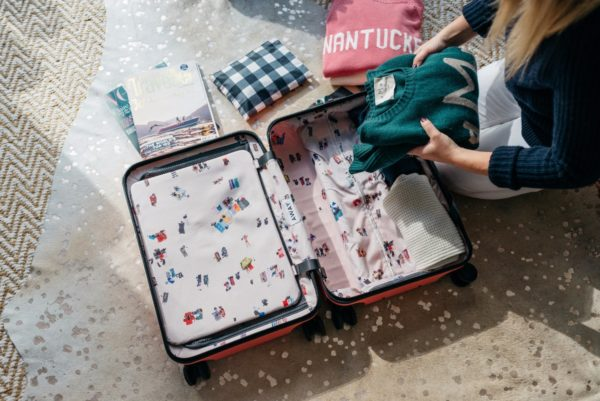 Travel and lifestyle blogger Bows & Sequins packing a pink hard shell suitcase.
