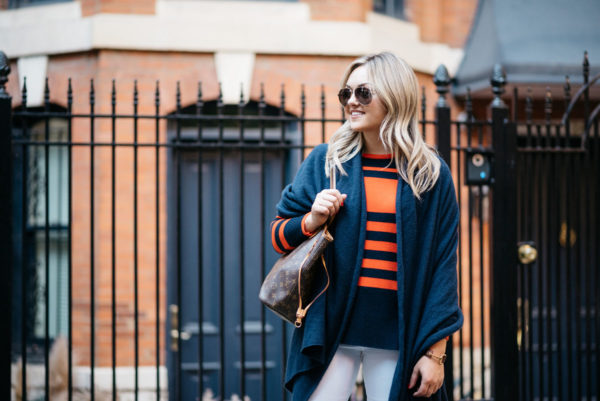 Bows & Sequins wearing Gucci aviators, an orange and blue striped sweater and a navy blue cashmere wrap with a Louis Vuitton Neverfull tote.