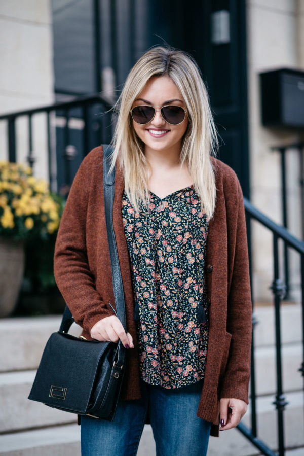 Bows & Sequins wearing Gucci aviators, an Old Navy slouchy cardigan, a floral blouse, and a black Lancel Pia bag.