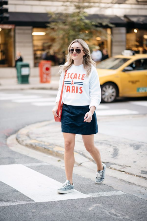 Chicago travel blogger Bows & Sequins wearing Gucci aviators, a French Disorder Paris sweatshirt, and an Old Navy blue suede skirt and Claudie Pierlot gingham sneakers with a Talbots red leather bag.