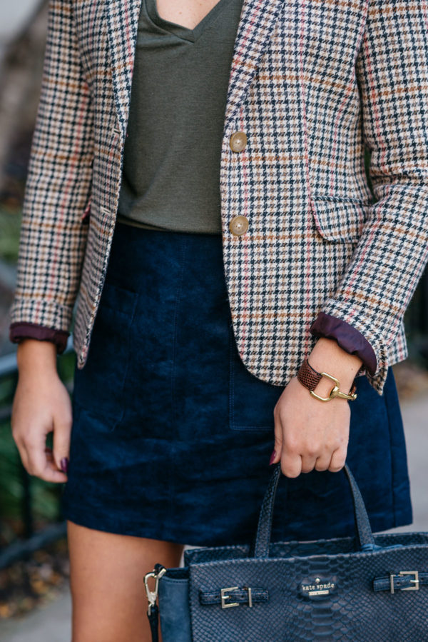 Bows & Sequins wearing a Joules houndstooth blazer, an Express olive green v-neck tee, and an Old Navy blue suede skirt with a Gucci leather cuff via Switch and a Kate Spade navy blue bag.