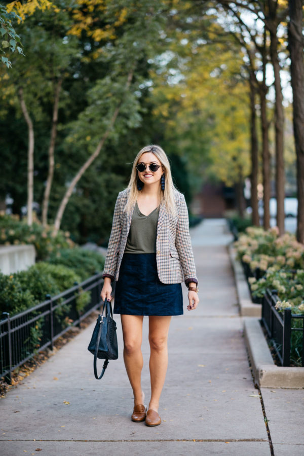 Fashion and lifestyle blogger Bows & Sequins wearing Illesteva sunglasses, Baublebar navy tassel earrings, Joules houndstooth blazer, Express olive green v-neck tee, and Old Navy blue suede skirt with a Kate Spade bag and a Gucci cuff bracelet via Switch.