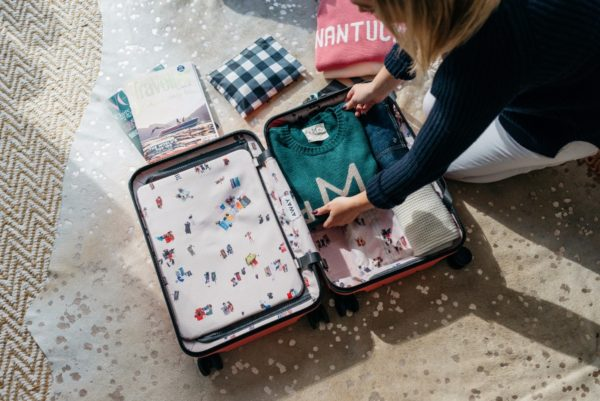 Travel and lifestyle blogger Bows & Sequins using a pink hard shell Away x Gray Malin suitcase.