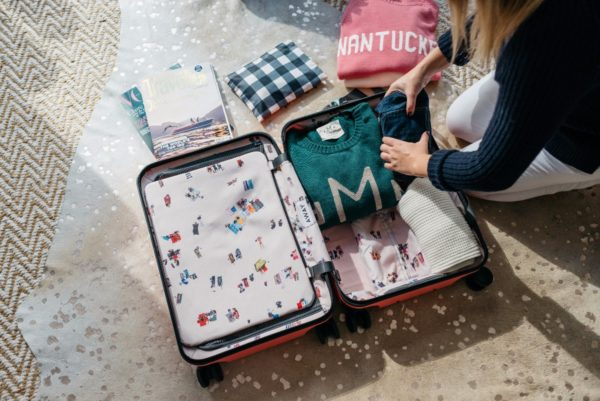 Bows & Sequins packing a pink hard shell suitcase.