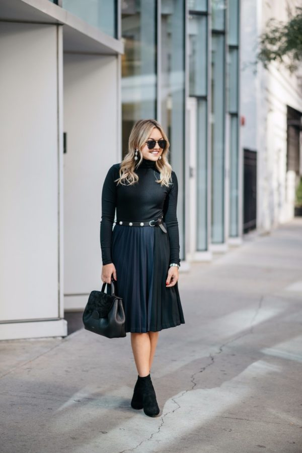 Chicago blogger Bows & Sequins wearing a J.Crew turtleneck bodysuit with a navy and black pleated midi skirt, Le Specs aviators, Baublebar silver earrings, a pearl studded belt, and black ankle booties.
