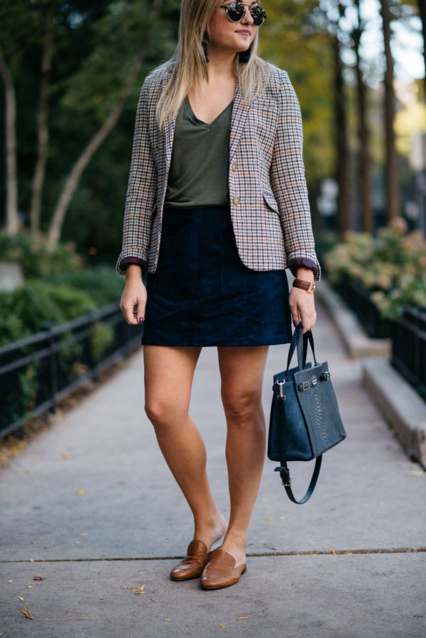 Bows & Sequins styling a work wear outfit: Joules houndstooth blazer, Express olive green v-neck tee, Old Navy blue suede skirt, and Dune London leather loafers with a Kate Spade bag.