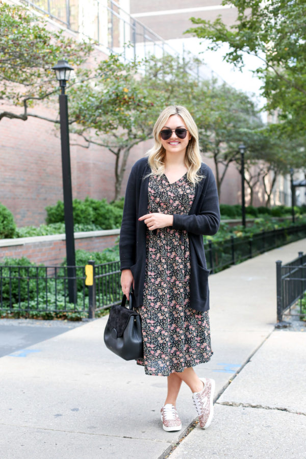 Bows & Sequins wearing a black cardigan, floral midi dress, and pink glitter sneakers with a Polene leather top-handle bag and aviators.