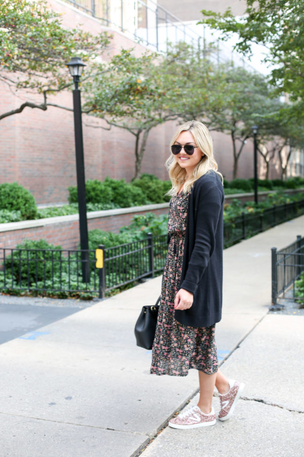 Bows & Sequins wearing matte aviators, a black cardigan, and a floral midi dress with pink glitter sneakers.