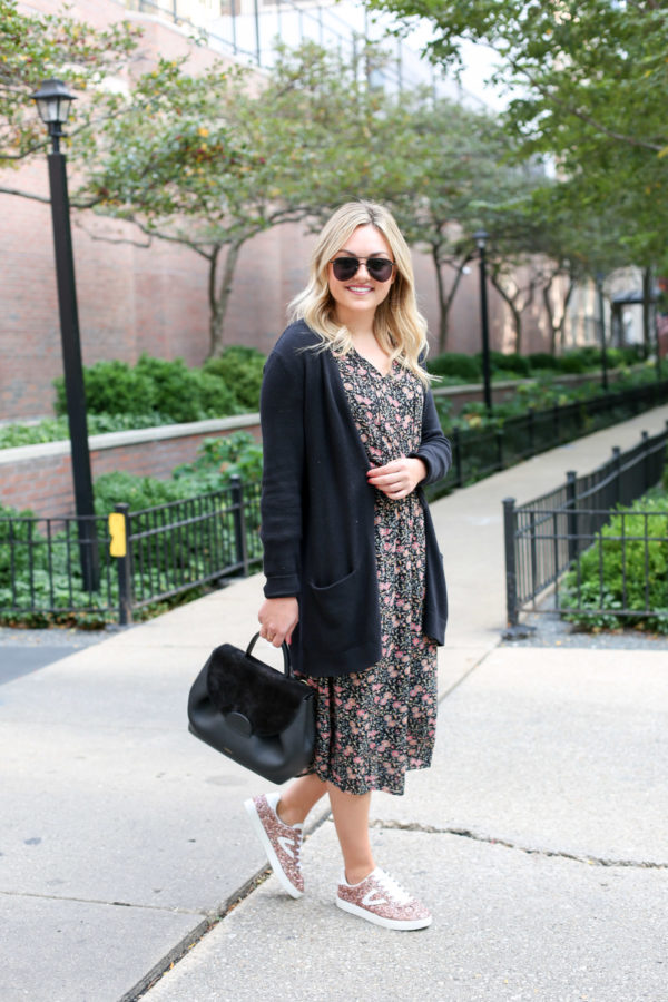 Chicago blogger Bows & Sequins wearing a black cardigan and a floral midi dress with a top-handle Polene bag and pink glitter sneakers.