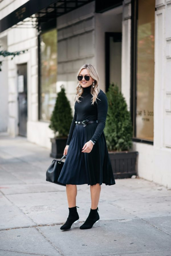 Bows & Sequins wearing Baublebar earrings, a J.Crew turtleneck bodysuit, a Leith pleated skirt, and Steve Madden lucite ankle boots.