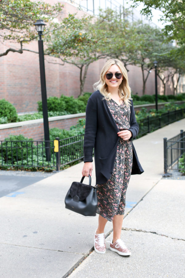 Bows & Sequins wearing matte aviators, a black cardigan, floral Old Navy midi dress, and Tretorn pink sneakers with a Polene top-handle leather bag.