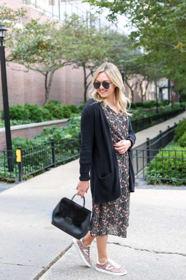 Chicago lifestyle blogger Bows & Sequins wearing matte aviators, a long black cardigan, floral midi dress, and pink sneakers.