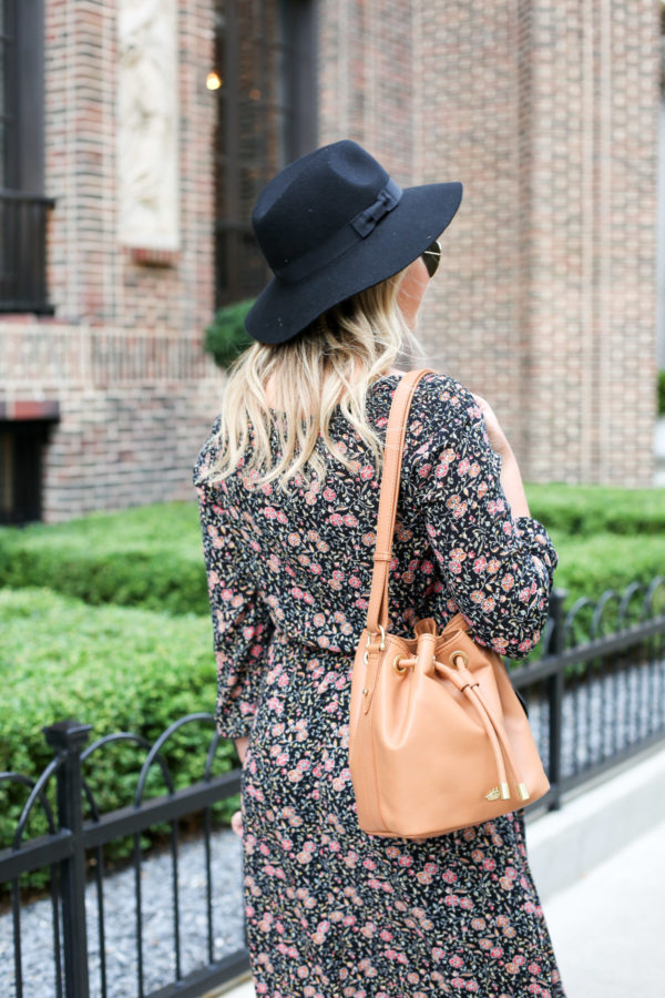 Bows & Sequins wearing a black hat from Old Navy, a floral dress, and a tan leather Brahmin bucket bag.