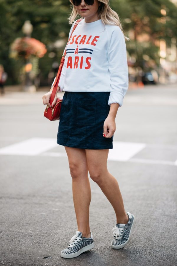 Bows & Sequins wearing Gucci aviators, a French Disorder sweatshirt, an Old Navy blue suede skirt, and Claudie Pierlot gingham sneakers with a Talbots red leather bag.