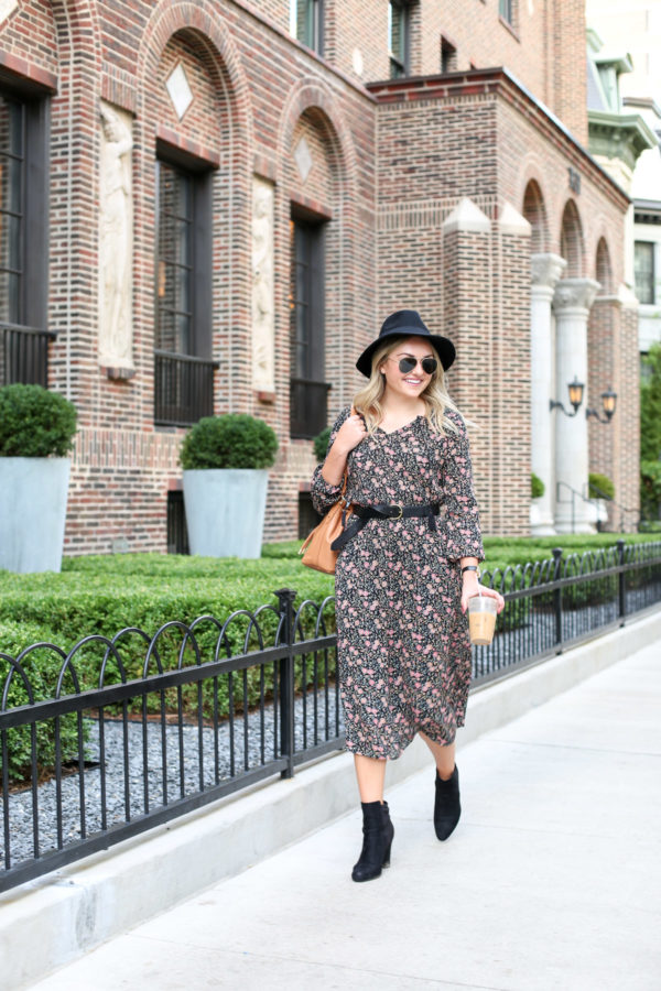 Bows & Sequins wearing a floral midi dress with a black hat, a leather Madewell belt, and black ankle booties with a Brahmin bag.