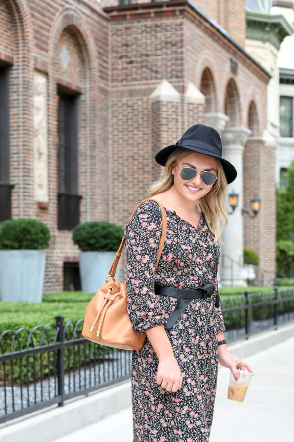 Chicago style blogger Bows & Sequins wearing a black hat, a floral midi dress, a Madewell leather belt, and a Brahmin bucket bag.