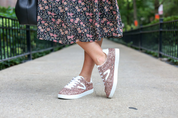 Bows & Sequins wearing a floral dress and Tretorn pink glitter sneakers.