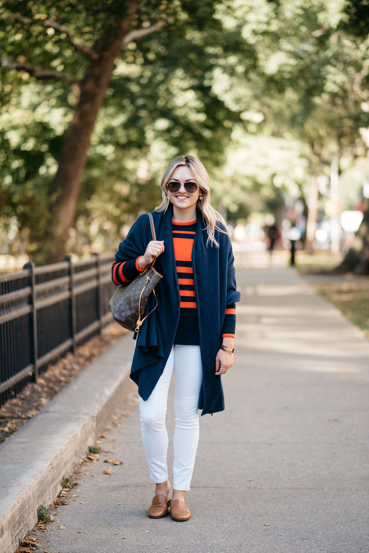 Chicago fashion and lifestyle blogger Bows & Sequins wearing a navy blue cashmere wrap, an orange and blue striped sweater, and white denim with Gucci aviators and Dune London leather loafers.