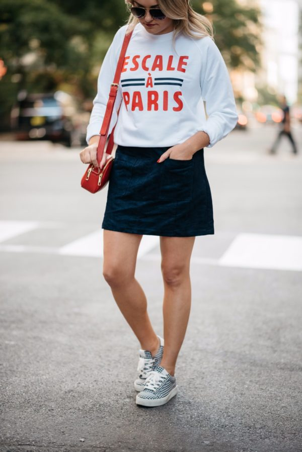 Fashion and travel blogger Bows & Sequins wearing a French Disorder Paris sweatshirt, Old Navy suede skirt, Gucci aviators, Claudie Pierlot gingham sneakers and a Talbots red leather bag.
