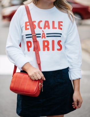 Chicago-based lifestyle blogger Bows & Sequins wearing a French Disorder sweatshirt with a Talbots red leather shoulder bag and a blue suede skirt.