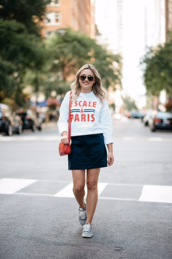 Fashion and lifestyle blogger Bows & Sequins wearing a Paris-inspired sweatshirt with Gucci aviators, an Old Navy suede skirt and Claudie Pierlot blue gingham sneakers.