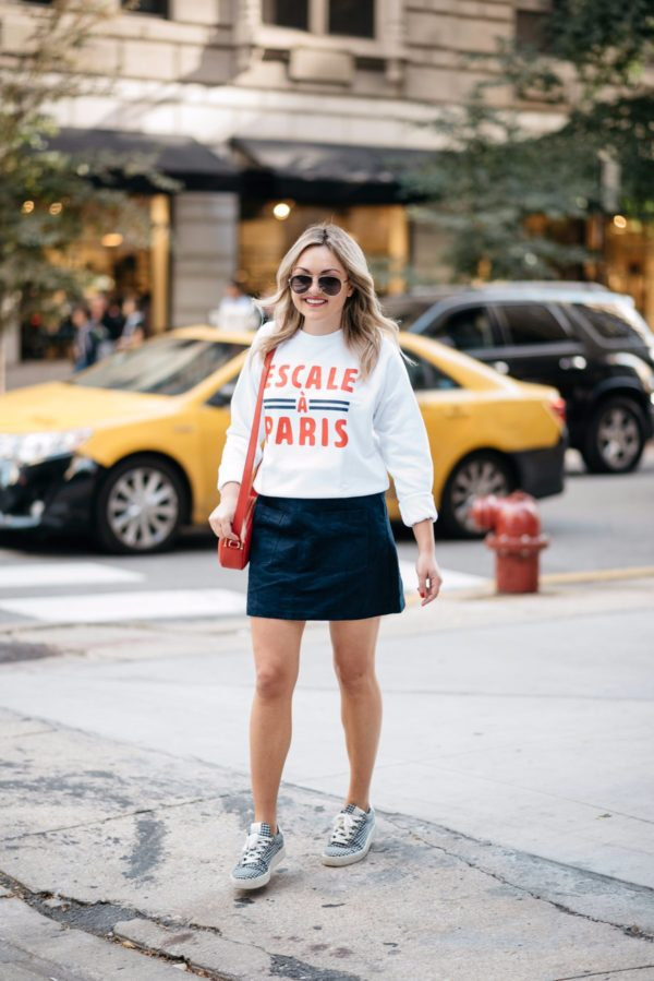 Fashion-focused lifestyle blogger Bows & Sequins wearing Gucci aviators, a French Disorder Paris sweatshirt, and an Old Navy blue suede skirt and Claudie Pierlot gingham sneakers with a Talbots red leather bag.