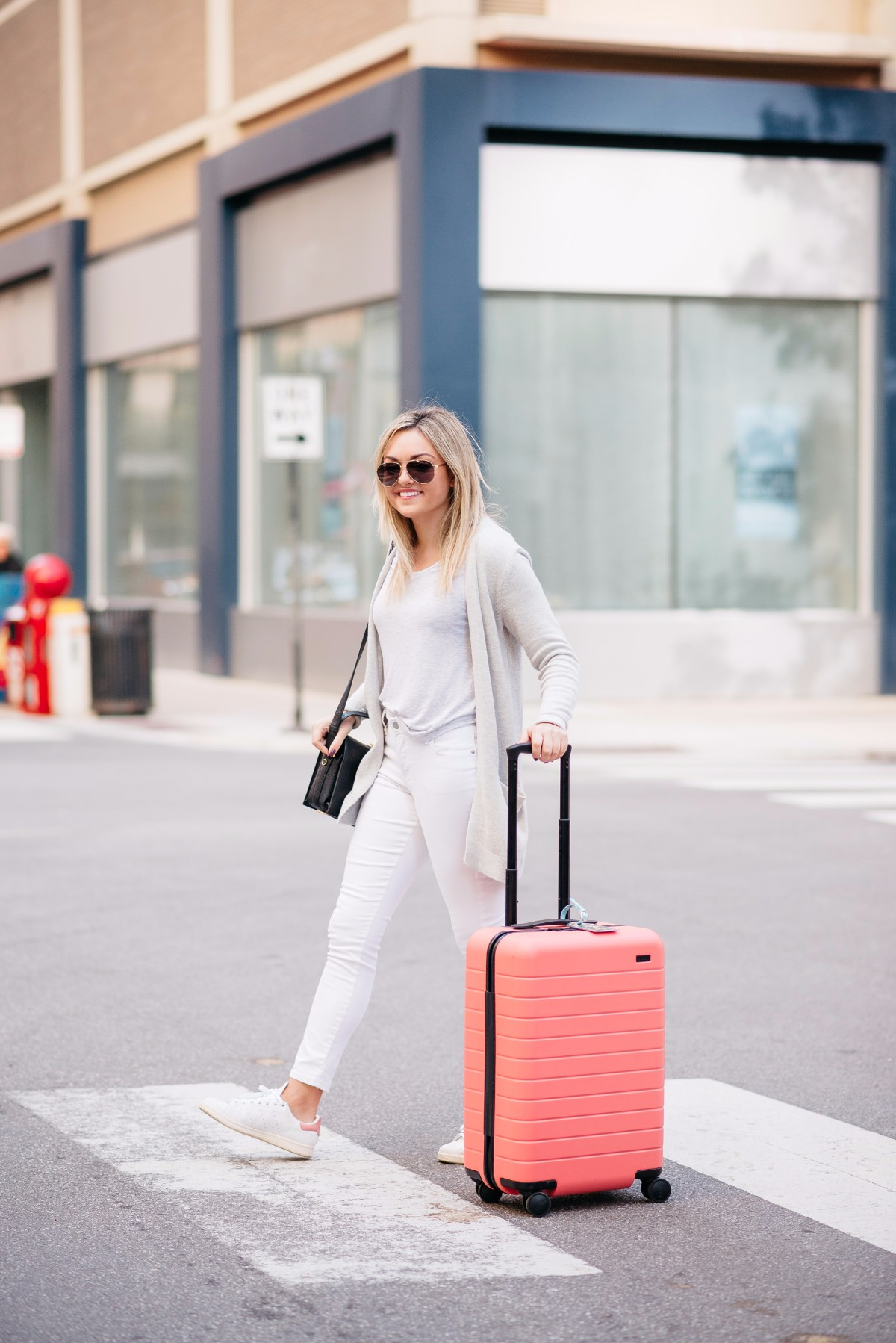 Bows & Sequins wearing an all white outfit with a pink hard shell carry on suitcase.