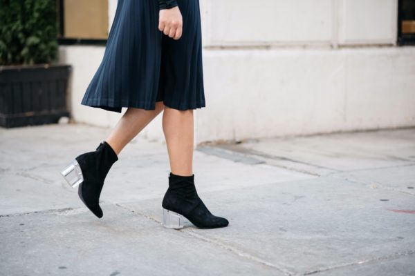 Chicago fashion and lifestyle blogger Bows & Sequins wearing a Leith navy and black pleated skirt and Steve Madden lucite ankle boots.