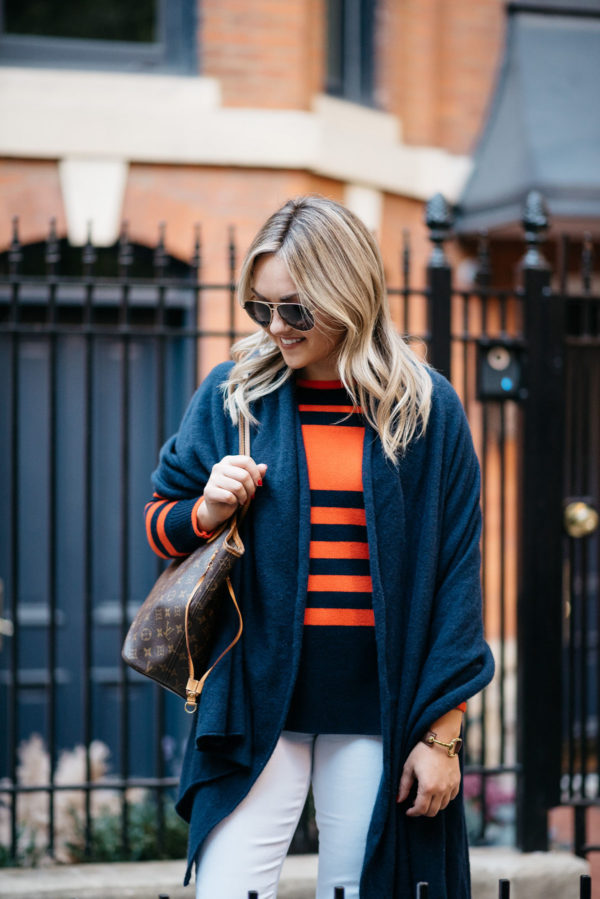 Bows & Sequins wearing Gucci aviators, a navy blue cashmere wrap, an orange and blue striped sweater, and a Louis Vuitton tote.