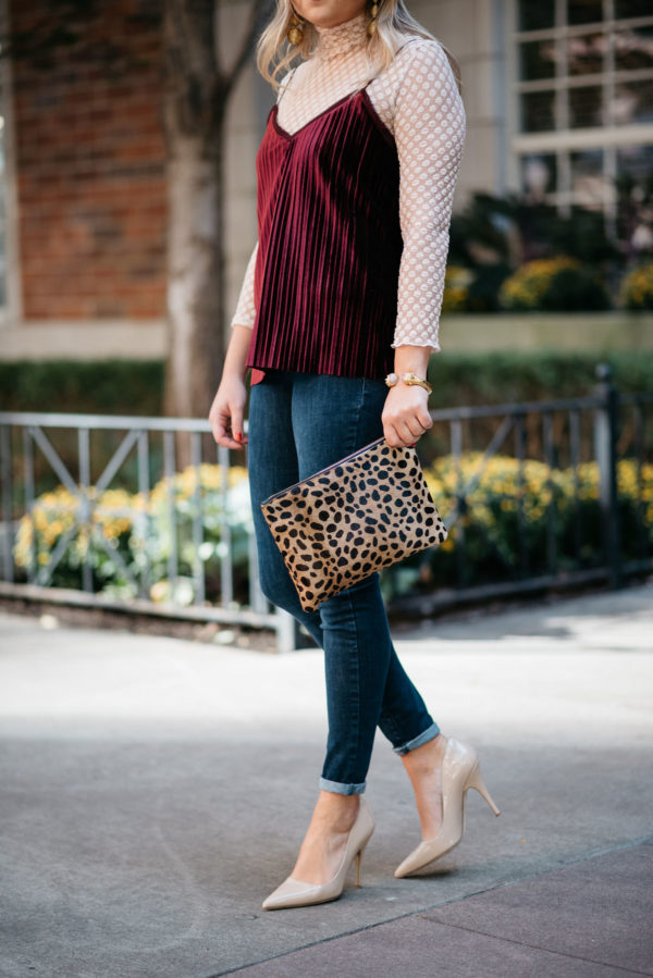 Bows & Sequins wearing a sheer lace turtleneck, a velvet cami, and skinny jeans with a Clare V leopard clutch, Kate Spade pumps, and a gold cuff.