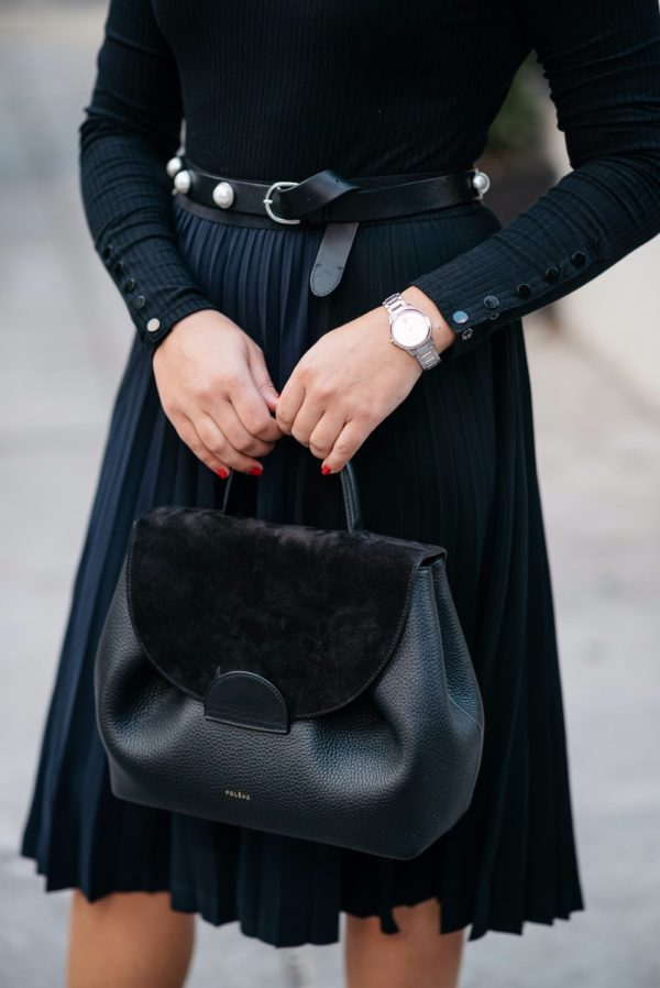 Bows & Sequins wearing a silver watch, a Claudie Pierlot pearl studded belt, a black and navy pleated skirt, and a Polene leather top-handle bag.