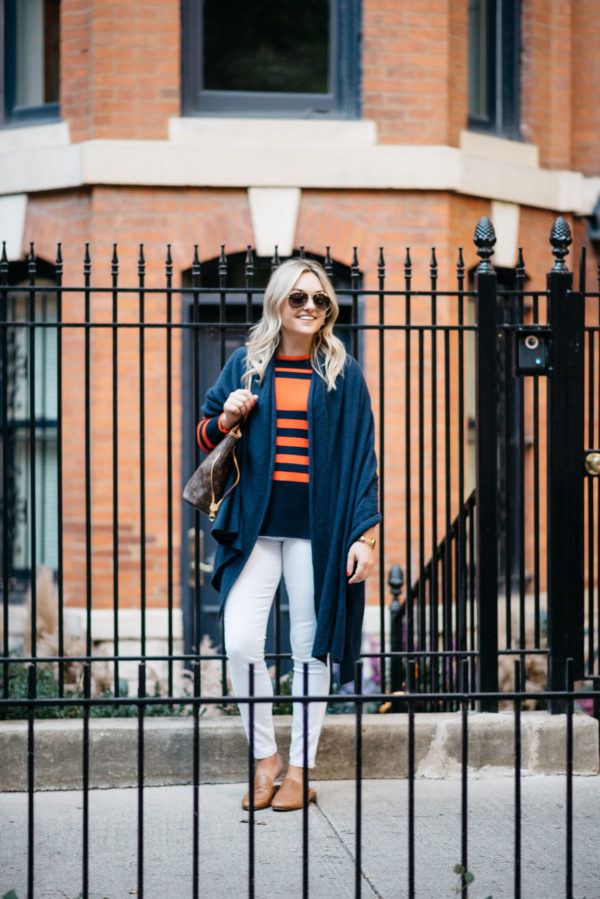 Chicago blogger Bows & Sequins wearing a navy blue cashmere wrap with a orange and blue striped sweater, Old Navy white denim and Dune London leather loafers.