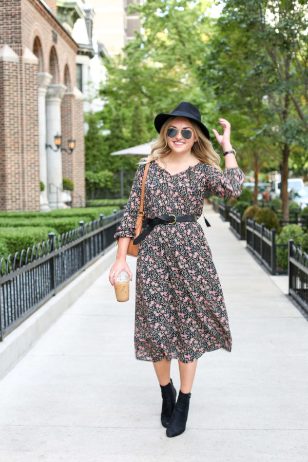 Chicago style blogger Bows & Sequins styling a floral midi dress from Old Navy with a black hat, black leather Madewell belt, and ankle booties.