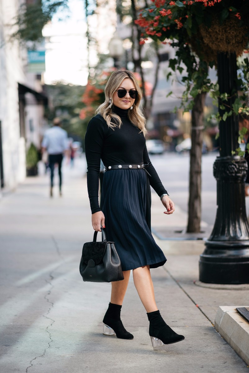 Fashion and lifestyle blogger Bows & Sequins wearing a J.Crew turtleneck bodysuit, a Claudie Pierlot pearl studded belt, a Leith navy and black pleated skirt, and a Steve Madden lucite ankle boots, with a Polene leather bag.